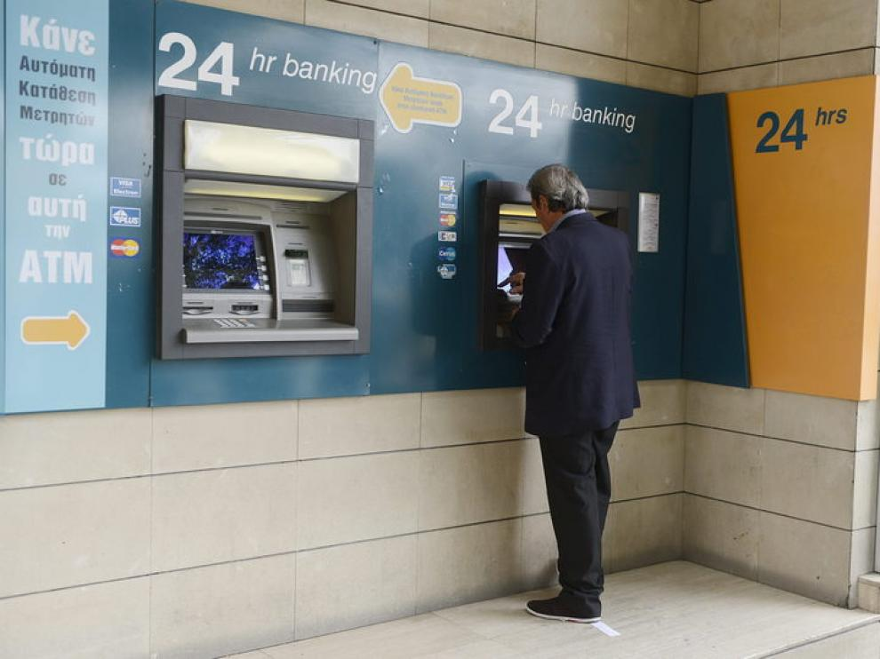 Un hombre retira dinero del cajero