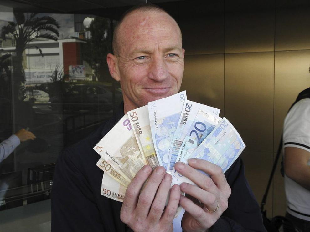 Un hombre muestra el dinero en efectivo que acaba de retirar de un banco chipriota