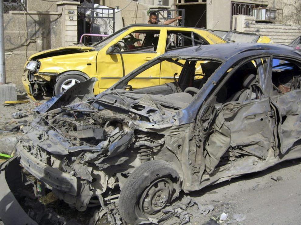 Dos hombres inspeccionan los coches dañados tras la explosión en Bagdad