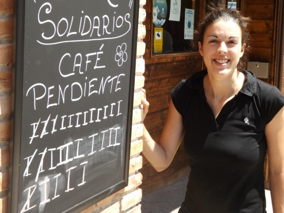 Estefanía Castán, camarera del bar La Fábrica de Huesca, ante la pizarra de cafés pendientes