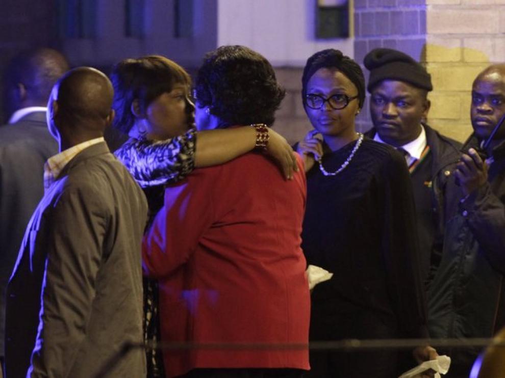 La exmujer de Mandela y su hija se abrazan a la puerta del hospital.