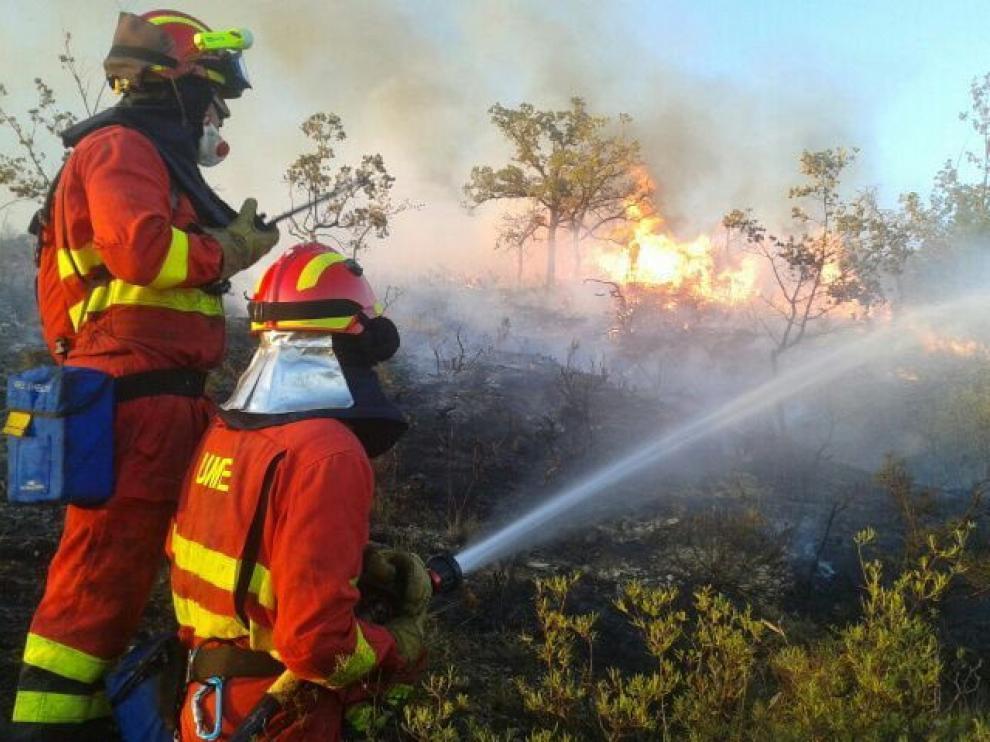 Dos miembros de la UME intentando sofocar un incendio