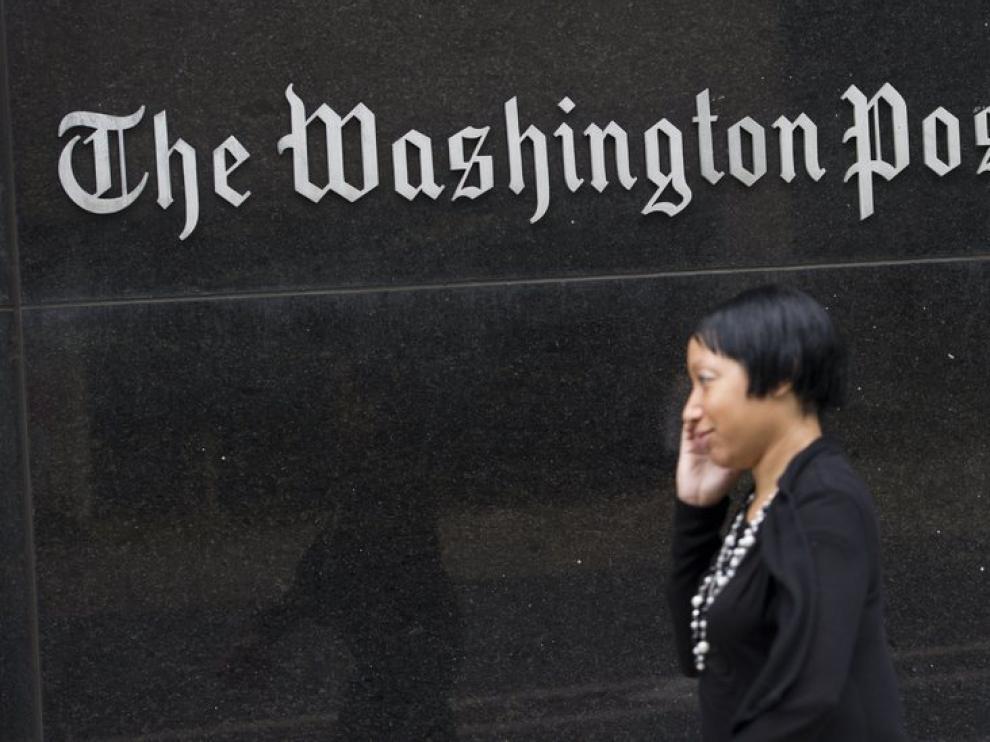 Una mujer camina junto a la sede del diario.