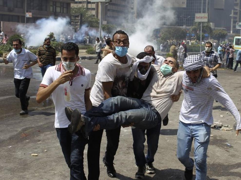Partidarios del expresidente Mursi evacúan a un herido.