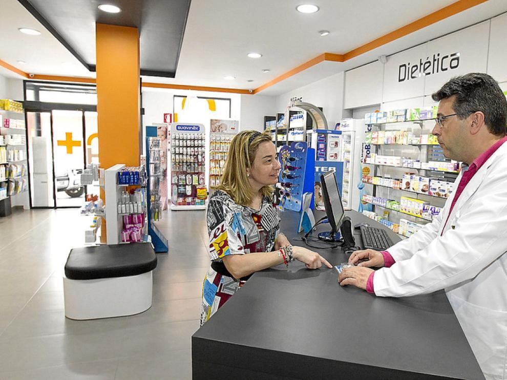 Antonio Hernández atiende a una paciente en su flamante farmacia.