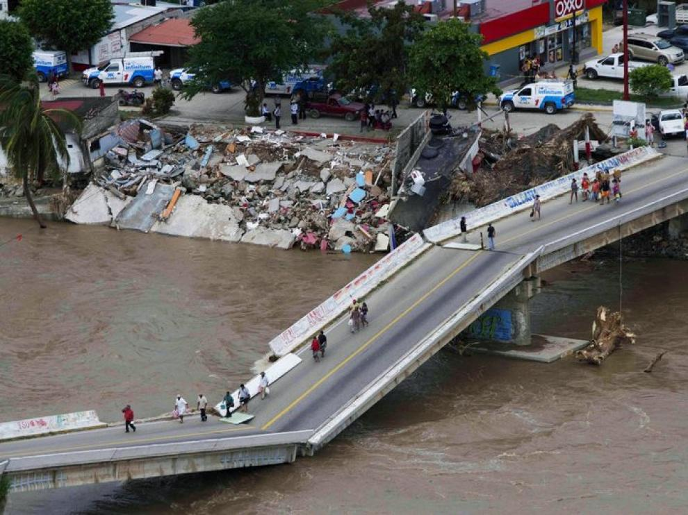 La gente camina por un puente roto en Acapulco