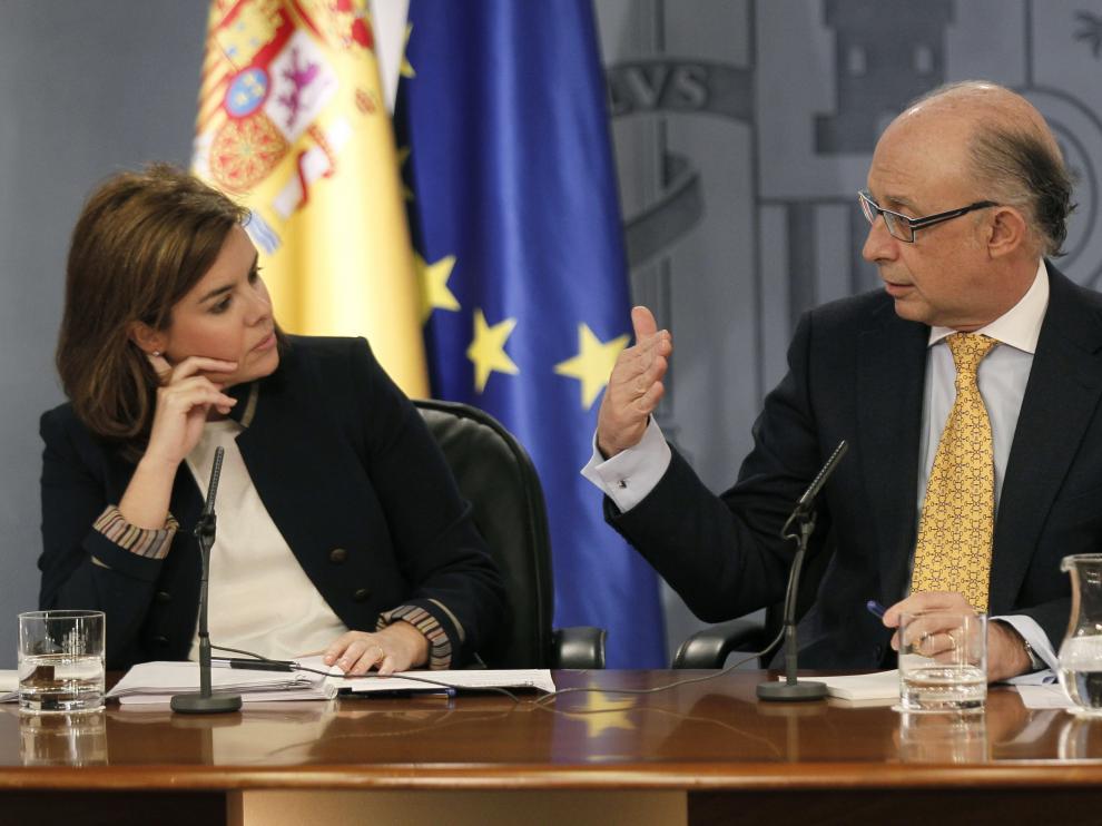 La vicepresidenta del Gobierno, Soraya Sáenz de Santamaría, escucha al ministro de Hacienda, Cristóbal Montoro