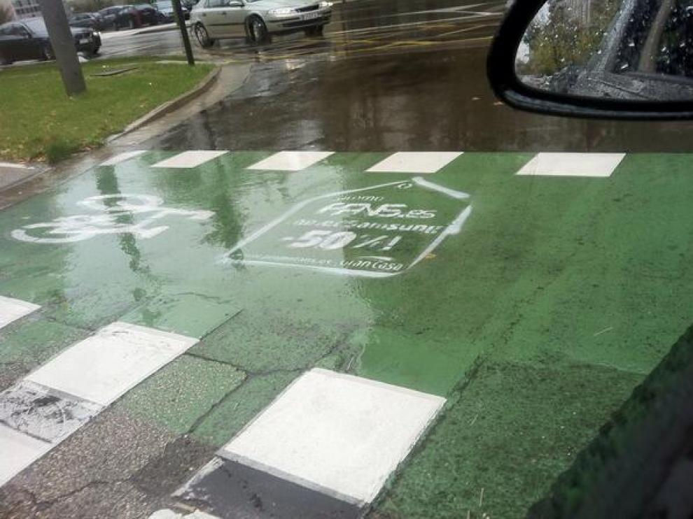 Pintada en el carril bici, junto al centro comercial.