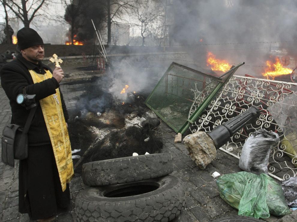 Un sacerdote alza una cruz frente a una barricada