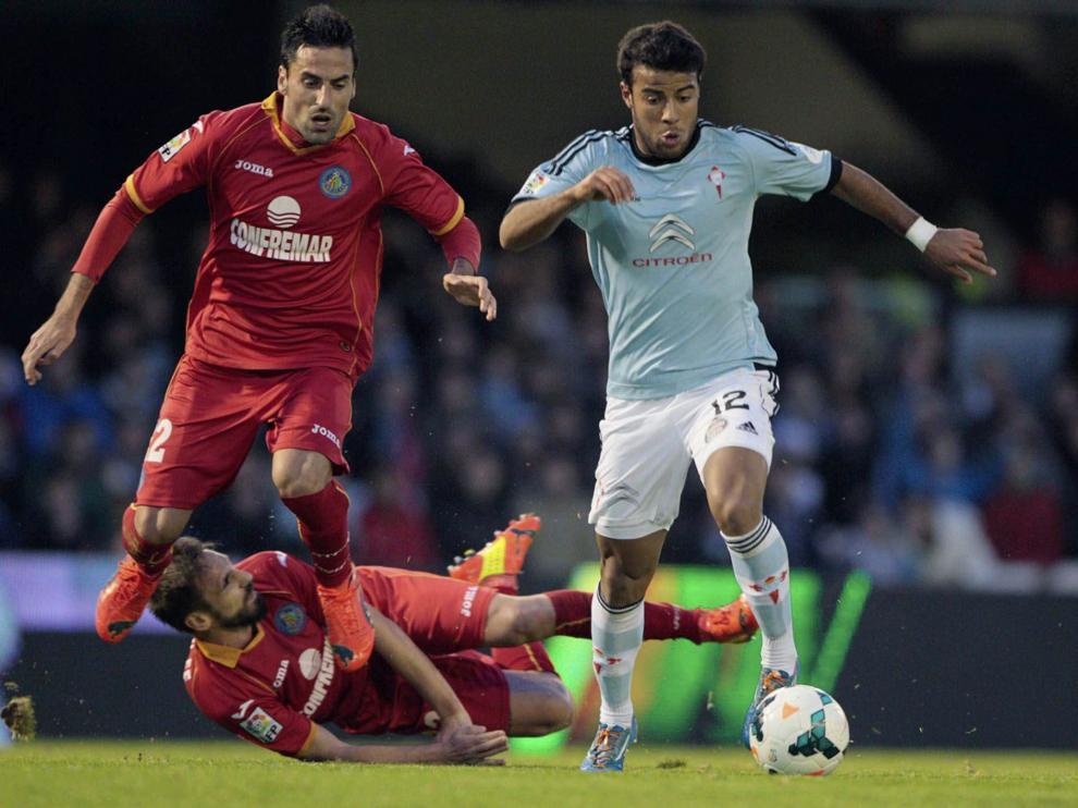 El centrocampista del Celta de Vigo Rafa Alcantara do Nascimento (d) controla el balón ante los jugadores del Getafe.