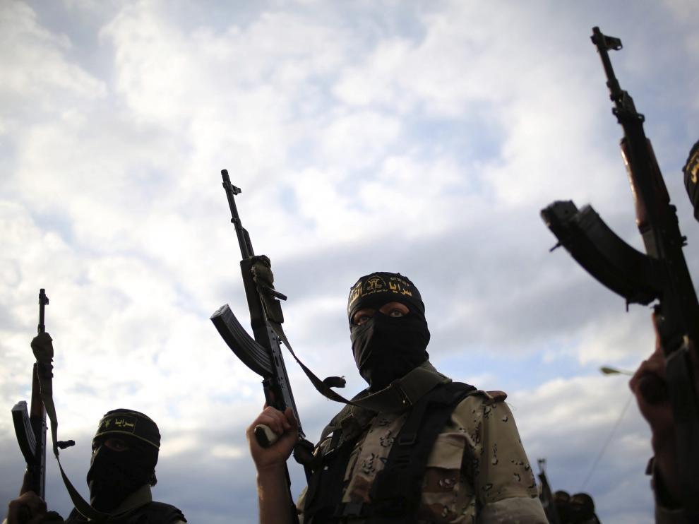 Varios militantes de la yihad islámica alzan sus armas durante un funeral