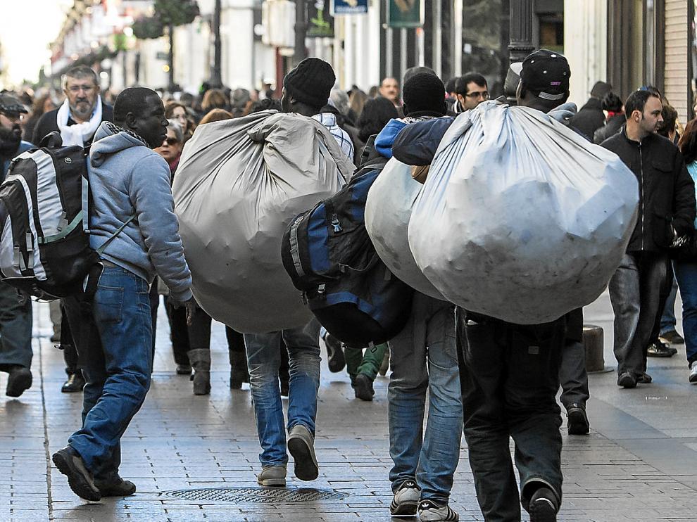 Cuatro manteros transportan su mercancía por la calle de Alfonso I de Zaragoza.