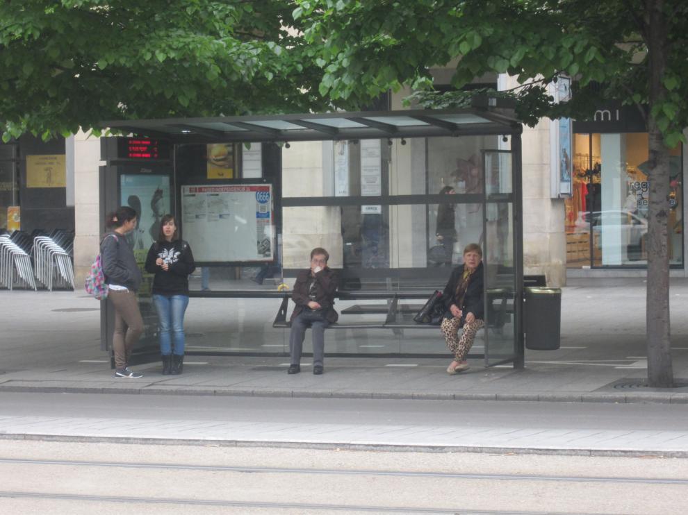 Varias personas esperan en una parada de bus durante uno de los paros