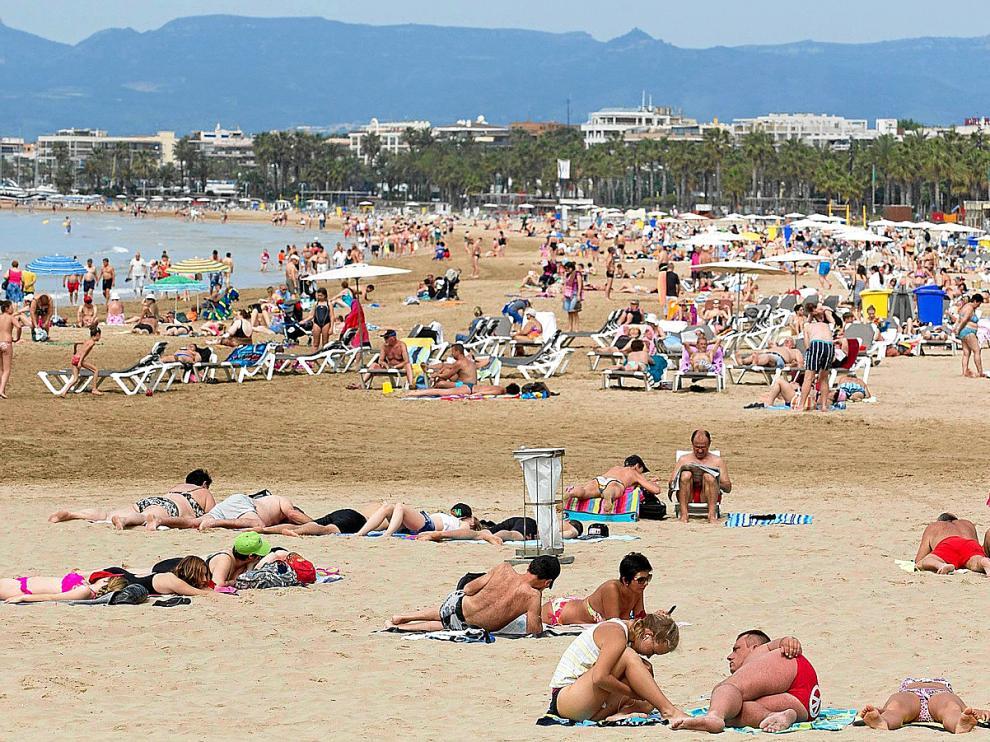 El buen tiempo atrae a los primeros bañistas a la playa de Levante de Salou, pero el grueso no llegará hasta julio o agosto.