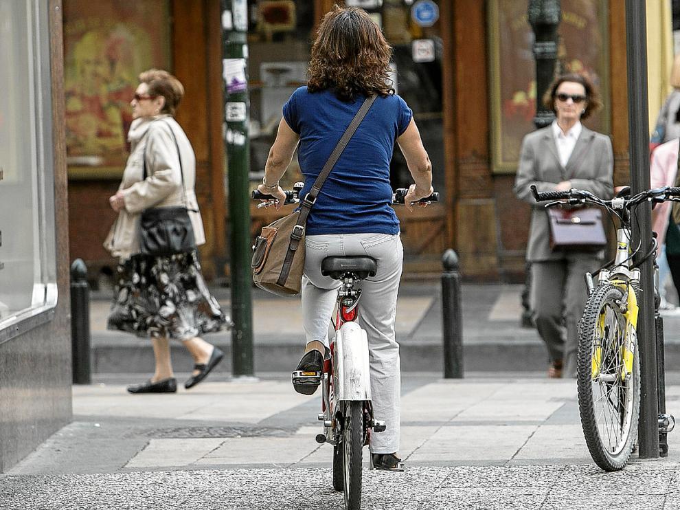 Una ciclista, circulando por la acera de la calle de San Jorge, en el Casco Histórico.