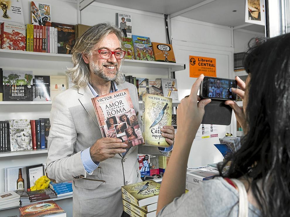 Víctor Amela firmó ayer ejemplares de sus novelas en la caseta de la librería Central.