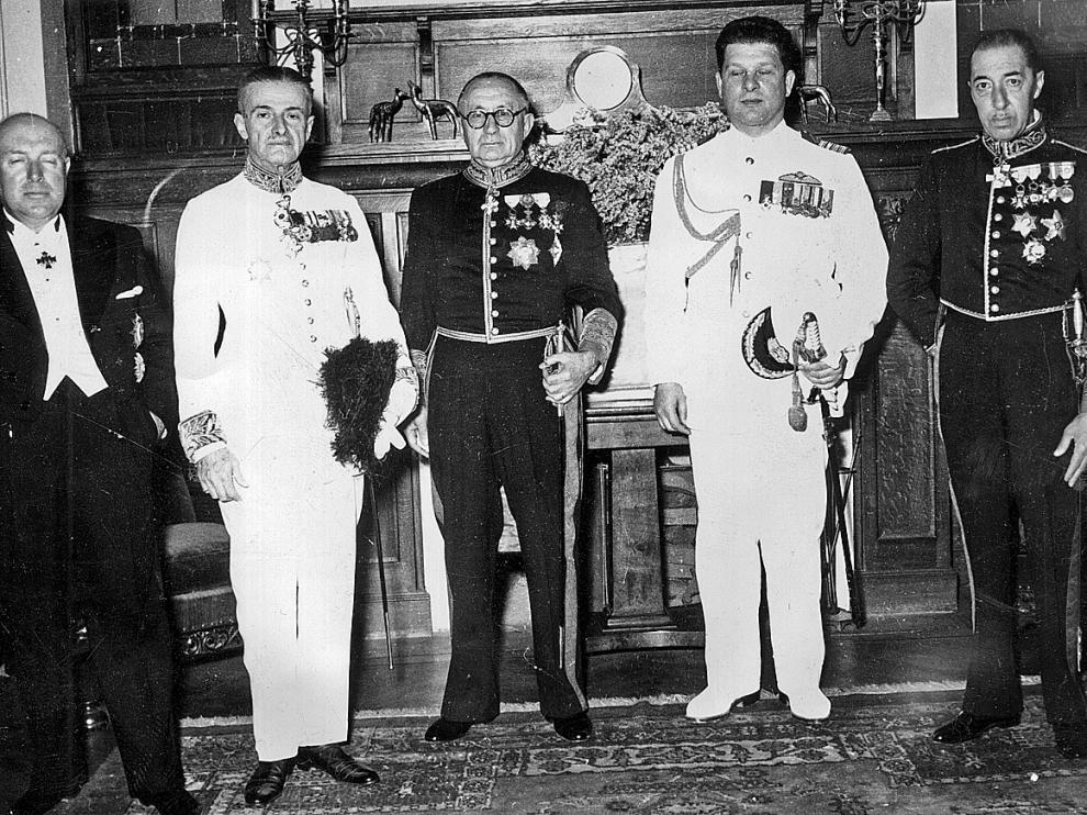 Sebastián Romero Radigales -destacado en un círculo-, con miembros del cuerpo diplomático y altos mandos militares en 1953. Debajo, pasaportes y salvoconductos como los que salvaron la vida a muchos judíos sefarditas.