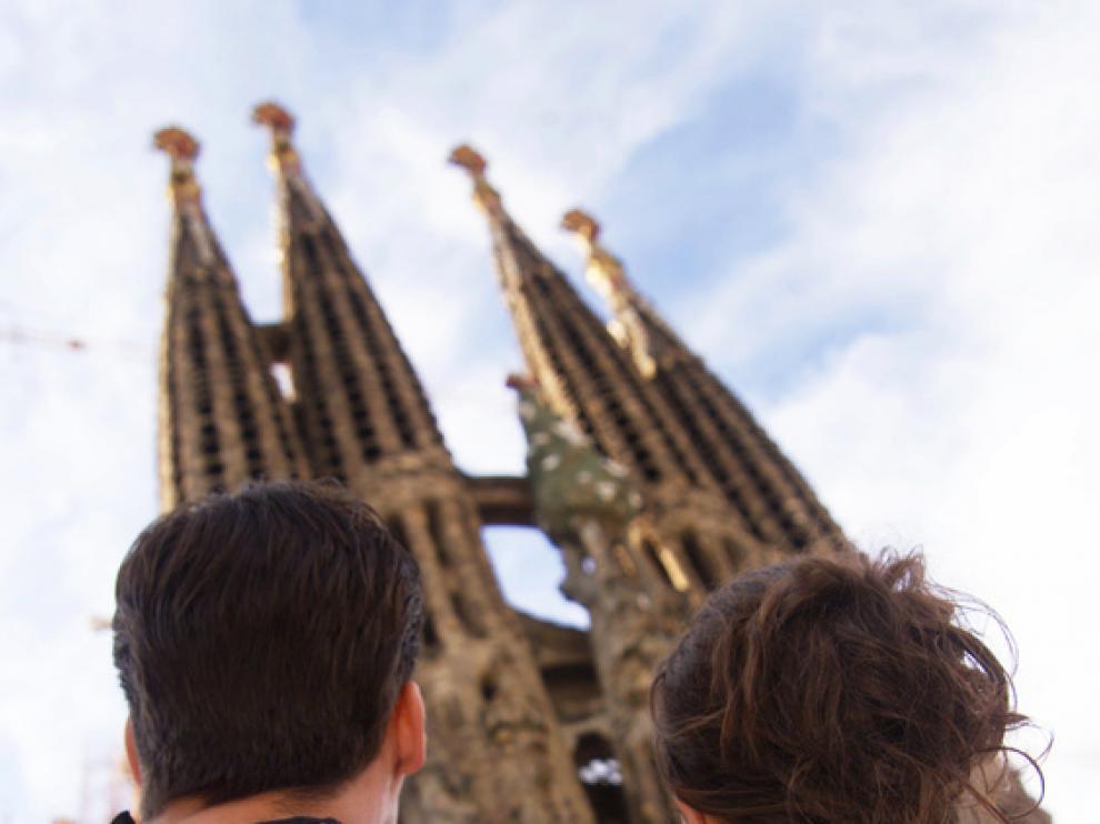 Una pareja contempla la Sagrada Familia de Barcelona.