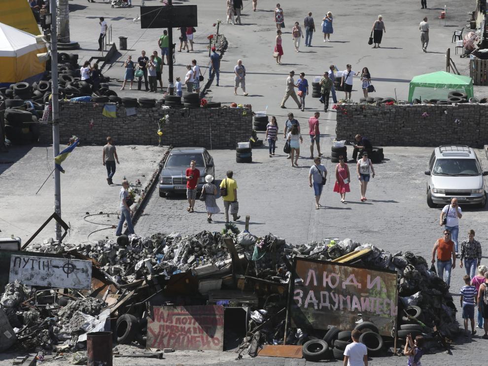 Varias personas caminan junto a las barricadas colocadas en Kiev, otras de las zonas de conflicto