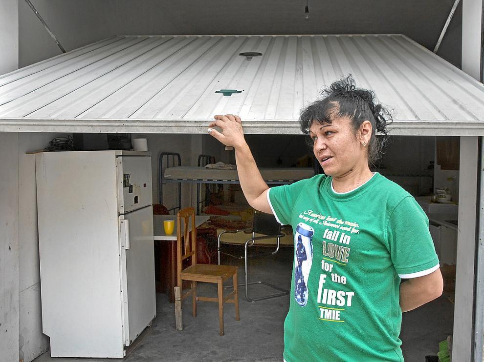 Carolina se apoya en la puerta del garaje que subarrienda a compatriotas. En el interior hay 12 camas.