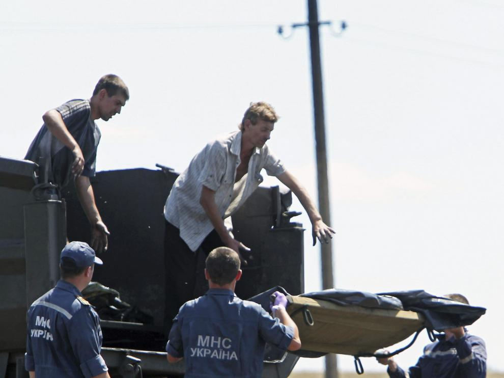 Trabajadores trasladan los cuerpos de los fallecidos en el accidente de avión