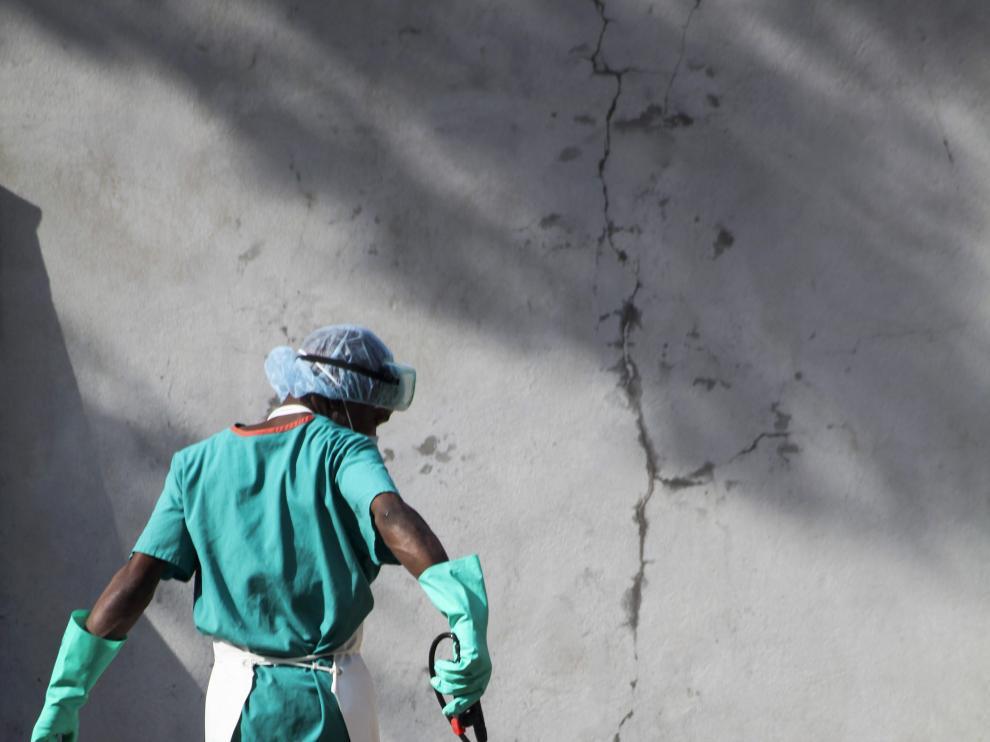Un trabajador sanitario rocía su calzado con desinfectante para evitar el contagio del virus del ébola en Liberia