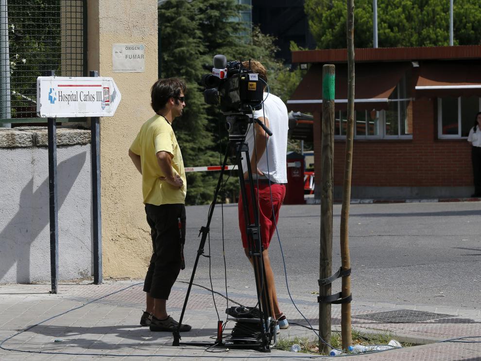 Dos reporteros de televisión graban en las inmediaciones del Hospital Carlos III
