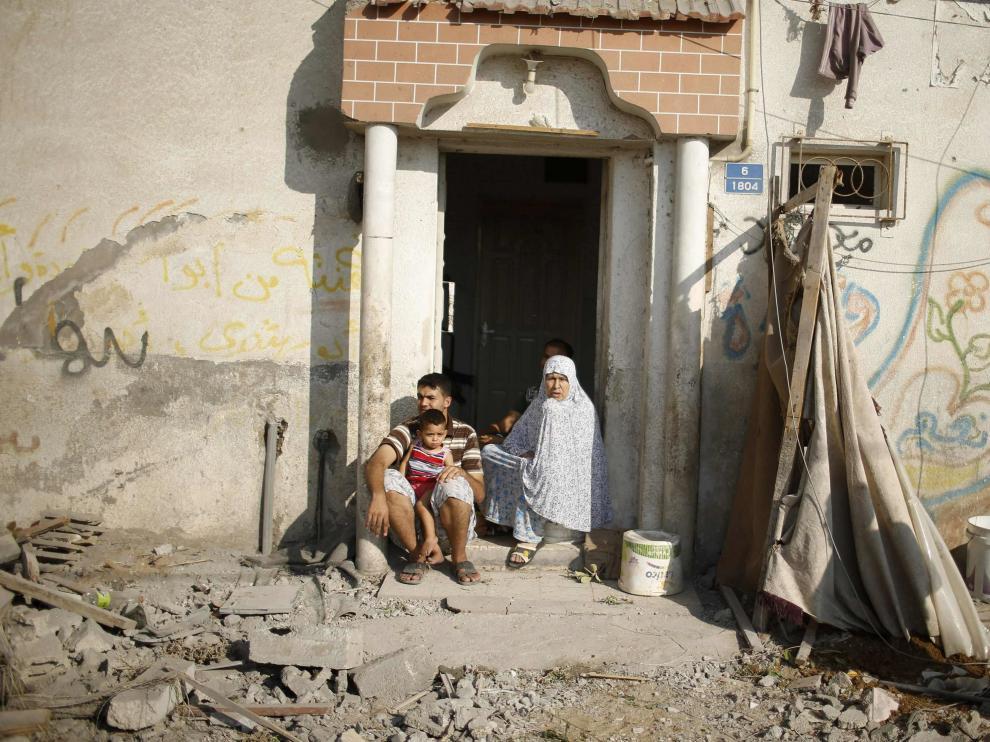 Una familia palestina, en la puerta de su casa dañada por los bombardeos