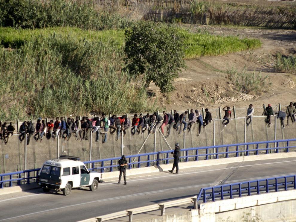 Inmigrantes encaramados en la valla de Melilla