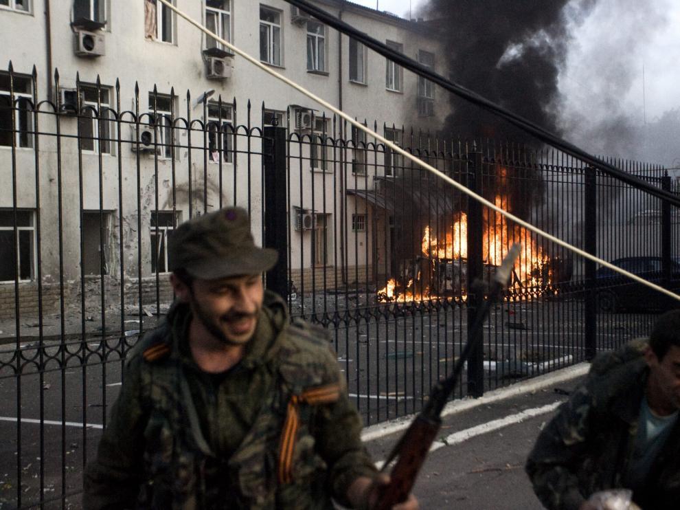 Los separatistas prorrusos se alejan de un coche en llamas