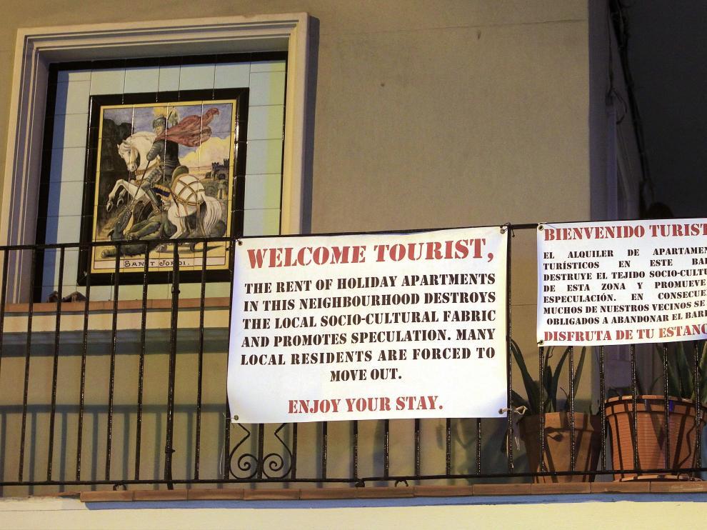 Cartel de los vecinos a los turistas en un balcón del barrio