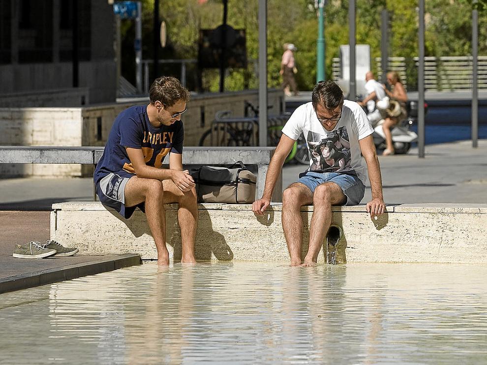 Dos ciudadanos refrescándose ayer en una fuente junto al paseo de Echegaray de Zaragoza.
