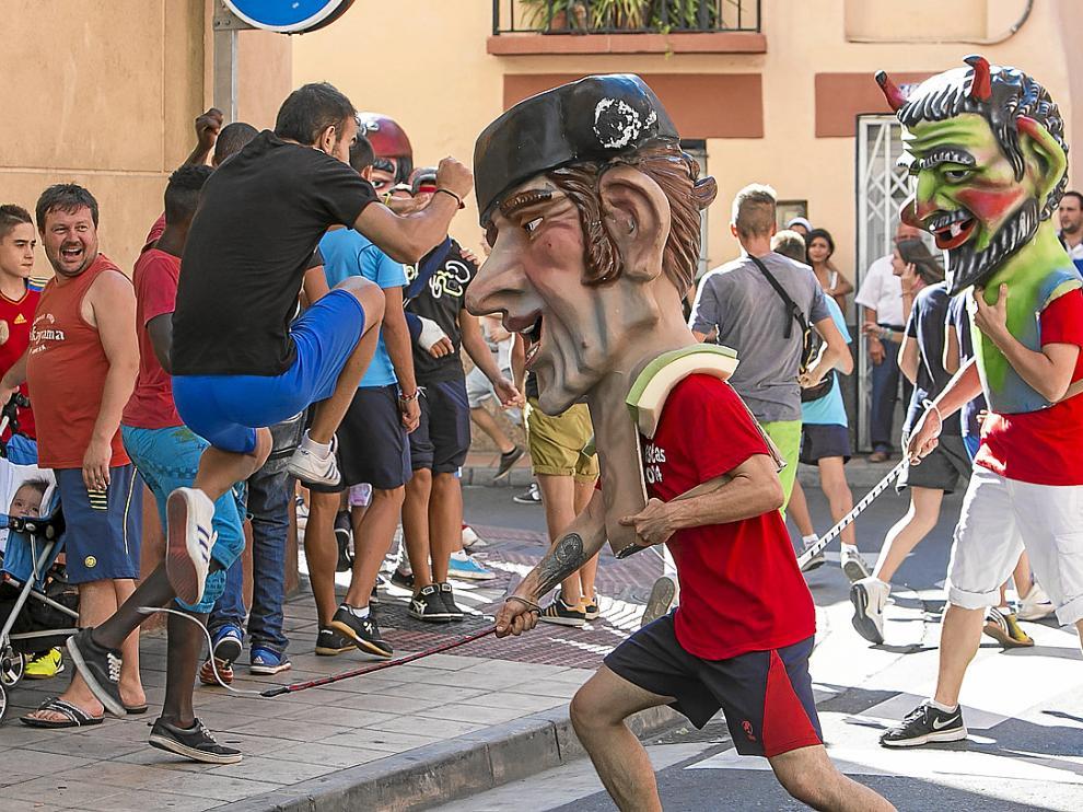 Un joven salta para esquivar el latigazo del cabezudo en la calle de Borja.