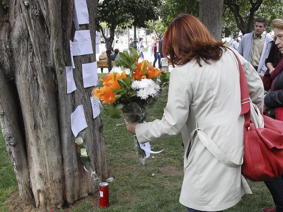 Una mujer deja un ramo de flores en el lugar de un suicidio, en Grecia
