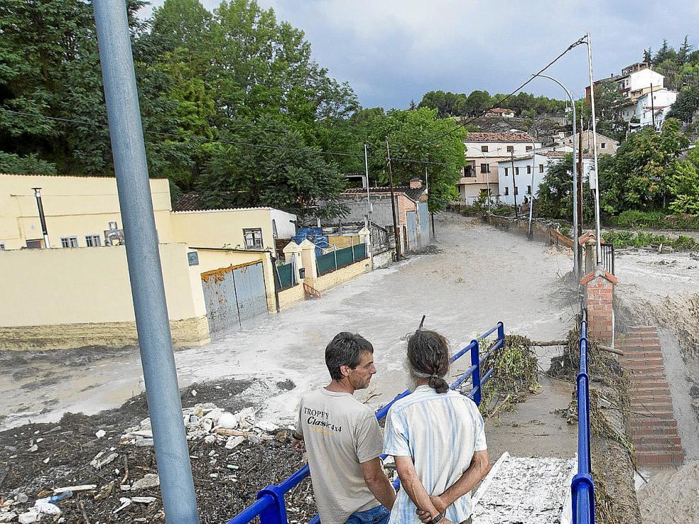 Dos vecinos observan el desbordamiento del barranco del Jorgito que forma una cascada mientras, a la izquierda, el agua se remansa al taponarse el desagüe hacia el Turia.