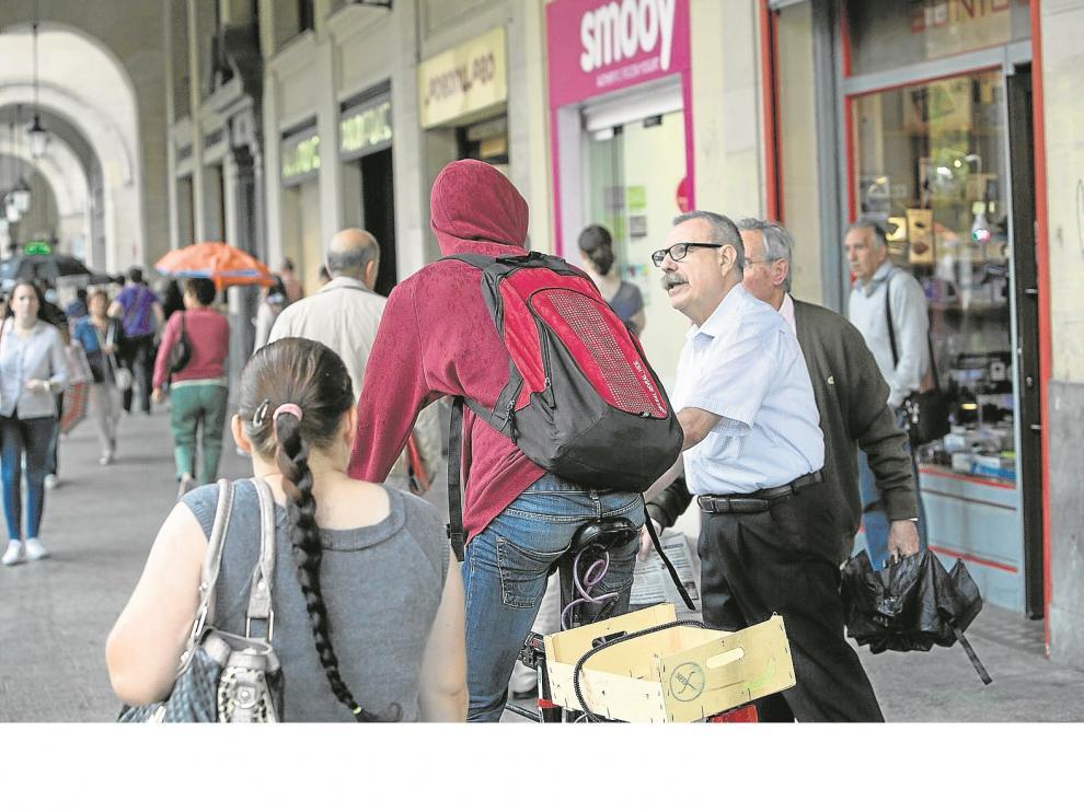 Dos peatones recriminan a un ciclista que estuviera circulando por los porches del paseo de la Independencia, ayer por la mañana.