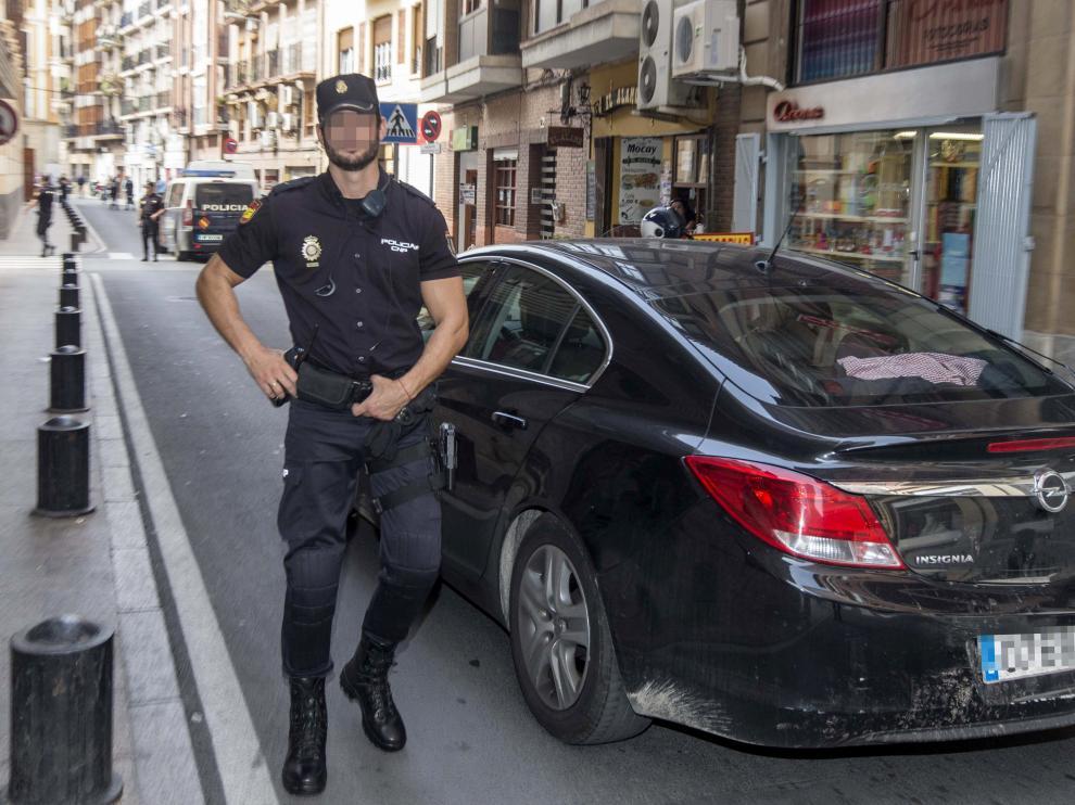 Un miembro de la Policía Nacional custodia el vehículo que traslada a dos de los seis policías detenidos