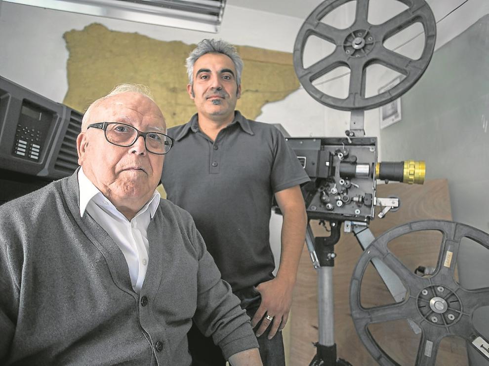 Generoso y Óscar Hernández, delante de un proyector portátil de 35 mm