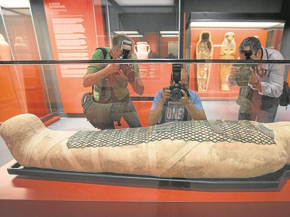 Tres fotógrafos, ante la momia de Pauiamen, hallada en Tebas, y datada entre los años 712 y 525 antes de Cristo.