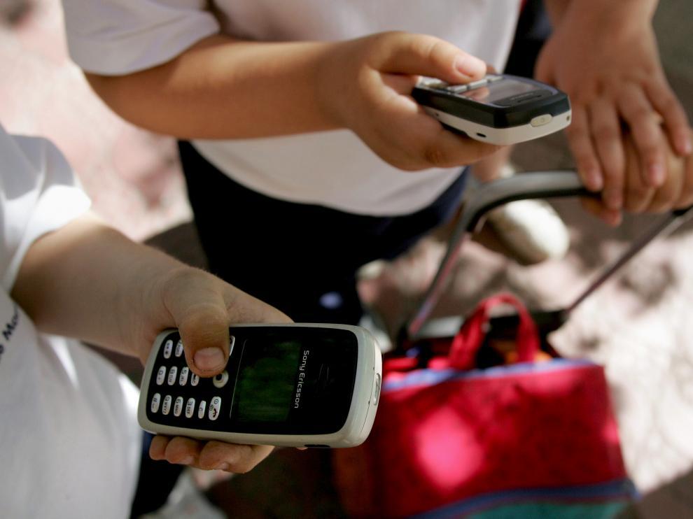Imagen de archivo de niños usando el móvil