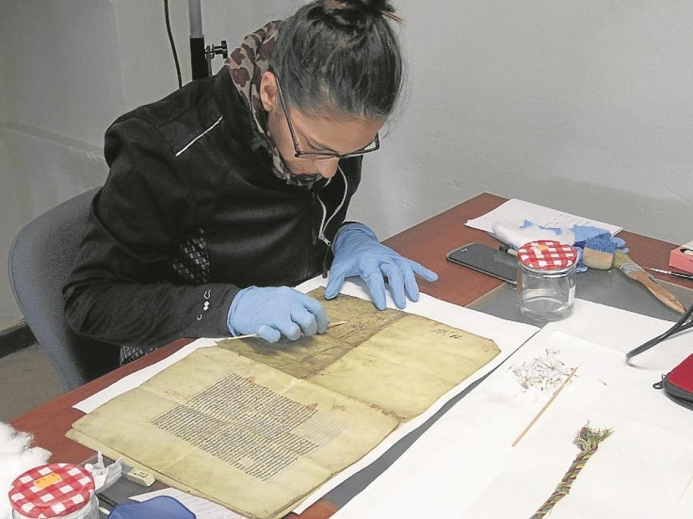Una restauradora trabaja en una de las joyas de la colección.