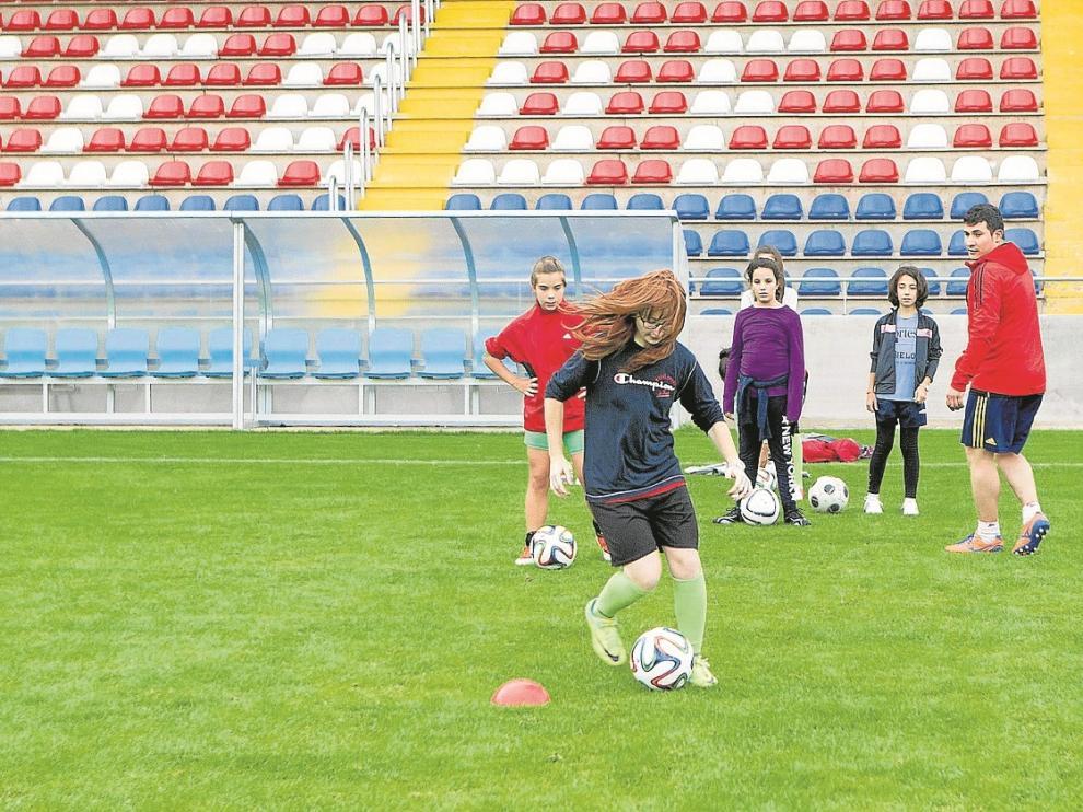 Una chica practica la conducción del balón en la jornada de puertas abiertas de la escuela de fútbol.