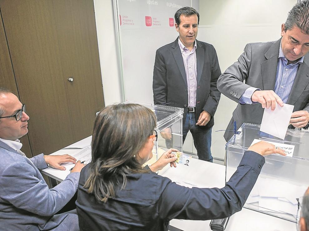 El candidato municipal, Javier Puy, vota en la sede, mientras espera el autonómico, Carlos Aparicio.