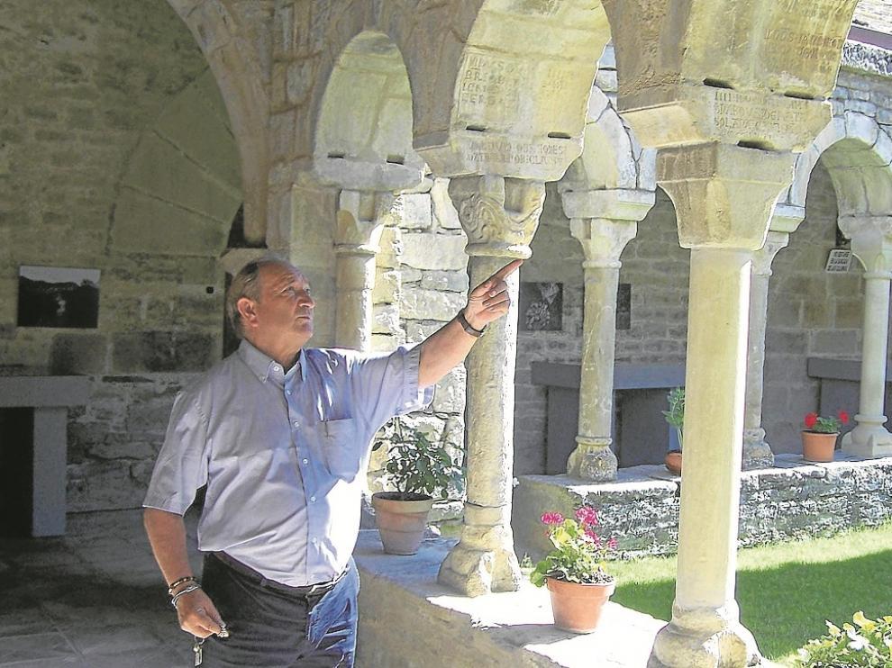 Aurelio Ricou, el párroco, ante algunas de las inscripciones afectadas.