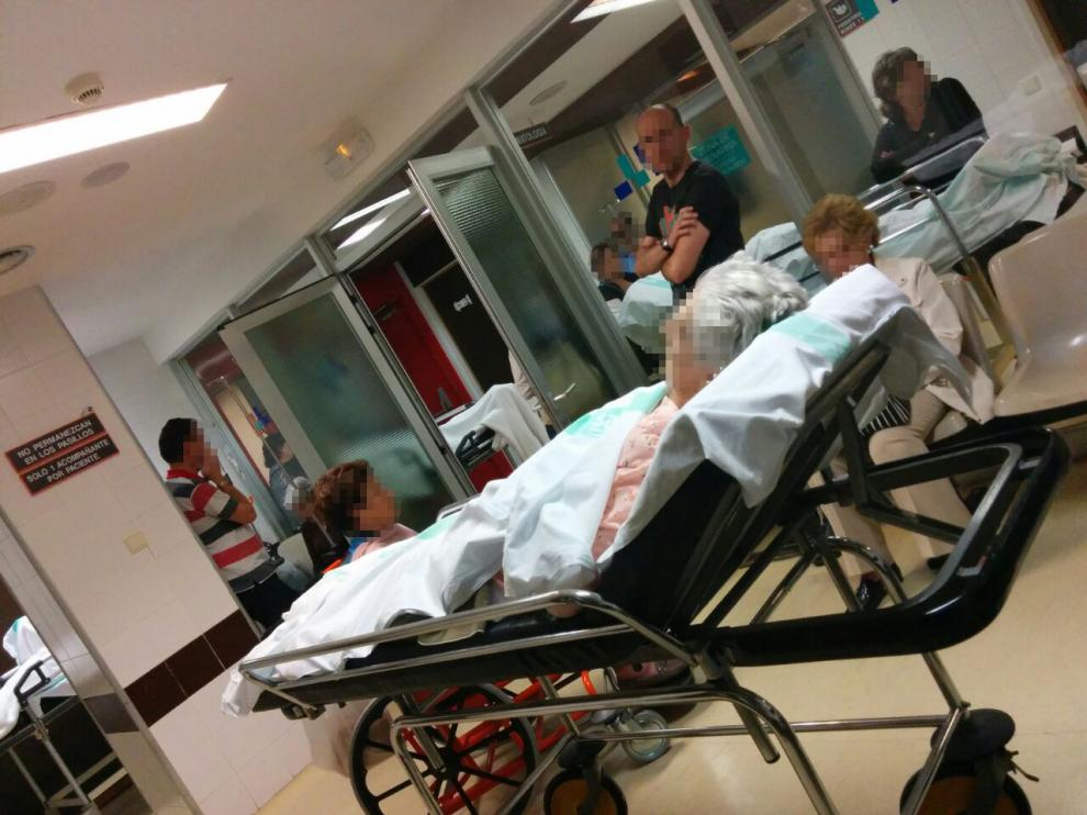 Varios pacientes en camilla esperan junto a sus familiares en los pasillos de Traumatología del hospital Clínico de Zaragoza, este jueves por la tarde.