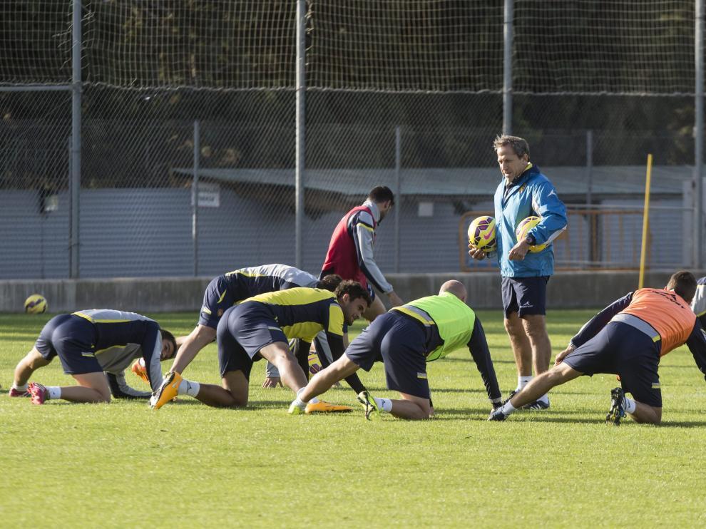 Víctor Muñoz charla con sus jugadores mientras estiran