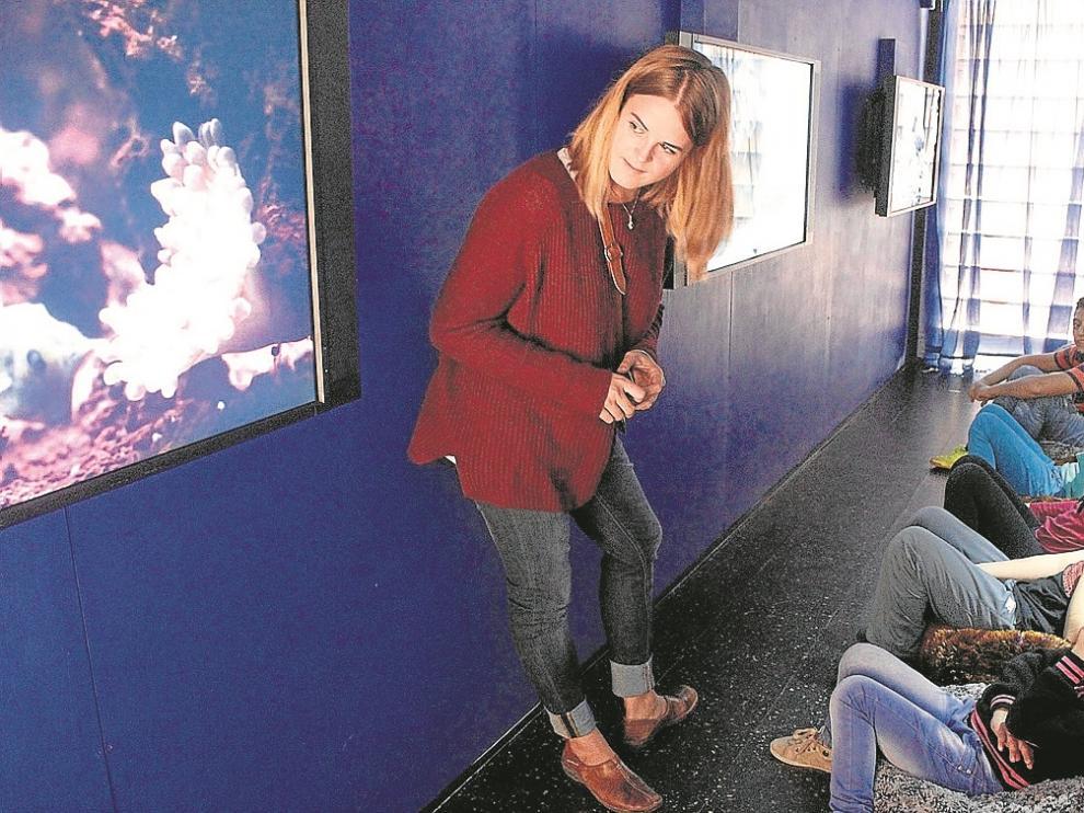 La guía Gloria Fernández, con varios niños en la sala de vídeos del Museo Móvil.