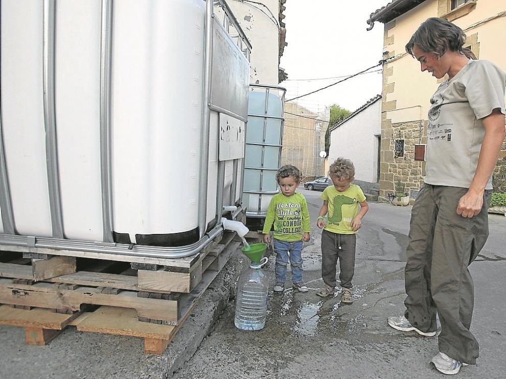 Beatriz Giménez y sus hijos, Lucas y Noel Bernúes, cogían ayer por la tarde agua de los depósitos provisionales que siguen instalados en Biscarrués.