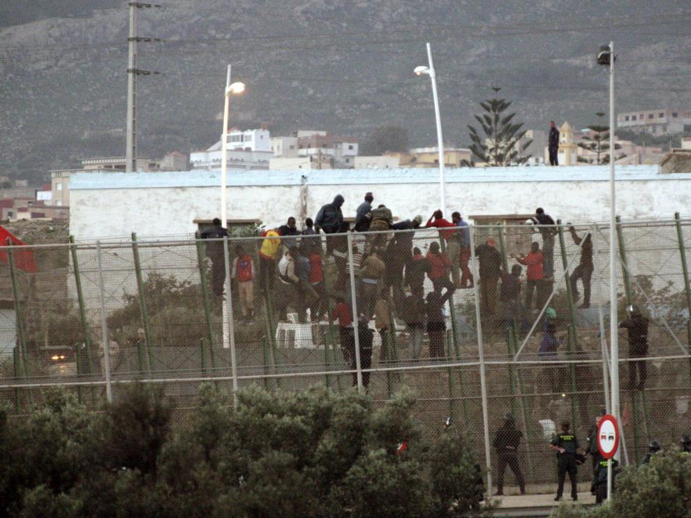 Inmigrantes encaramados en la valla de Melilla este viernes