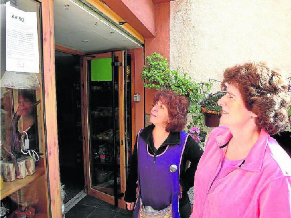 Dos vecinas de Santa Eulalia leen el bando que informa de la prohibición de beber del grifo.